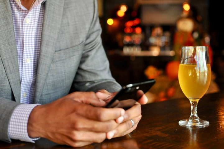 man with beer and phone in hand