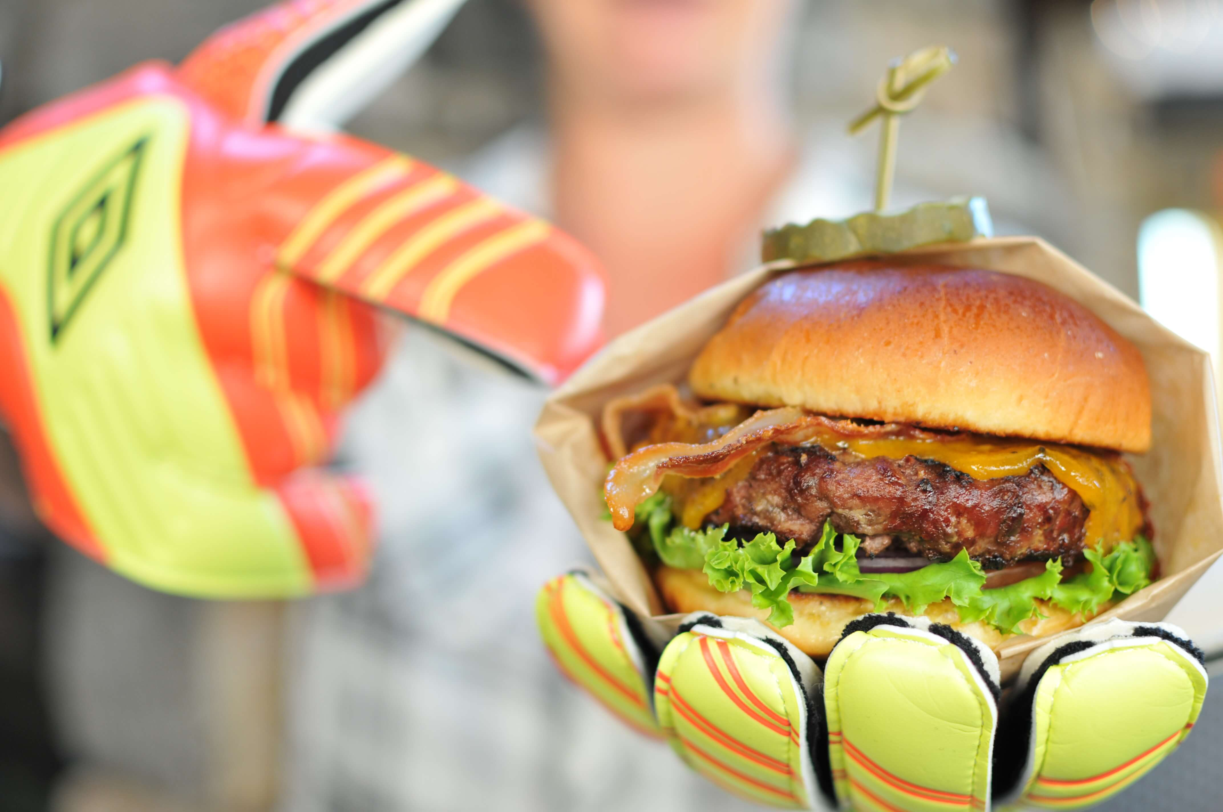 person holding a burger with soccer gloves